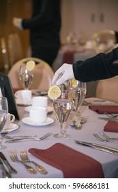Waiter Putting Sliced Lemon on Glass of Water