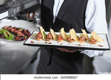 The waiter with the ready prepared dishes in the restaurant kitchen.
