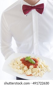 waiter with red bow tie and with plate of pasta with sauce, good appetite