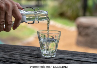 A waiter in a restaurant pours fresh water from a bottle into a glass, close up, outdoors
