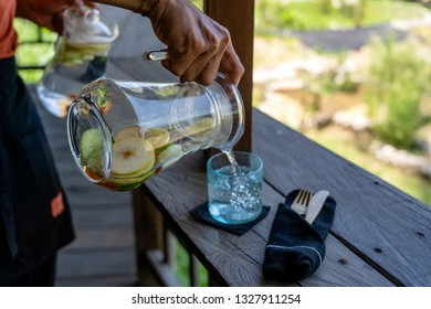 A waiter in a restaurant pours fruit water from a carafe into a glass, close up