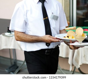 Waiter at the restaurant serves meals.