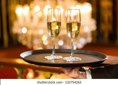 Waiter served champagne glasses on a tray in a fine dining restaurant, a large chandelier is in Background