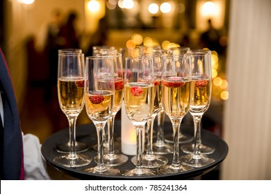 Waiter served champagne glasses on a tray in a fine dining restaurant