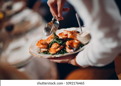 Waiter serves shrimp with arugula
