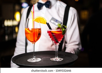 The waiter serves two cocktails on a tray. Close-up orange and red cocktails with orange and mint.