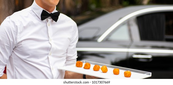 Waiter serving appetizers at a luxurious gathering.
