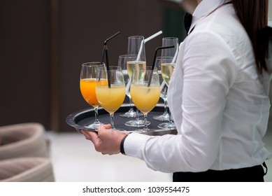 Waiter serving apple juice and alcohol drink
