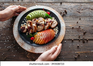 Waiter serving baked veal for retail. Chief decorating food for presentation in restaraunt. Waiter serving baked veal with fresh fruits.
