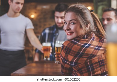 Waiter Serving Beer at a Pub. Group Of Hipster Friends Drinking Beer