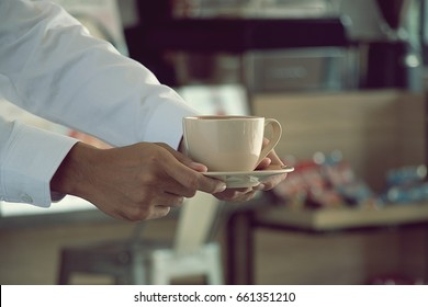 Waiter is serving coffee