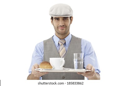 Waiter serving coffee and croissant, smiling, looking at camera.