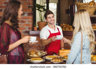 Waiter serving a coffee to a customer at the coffee shop