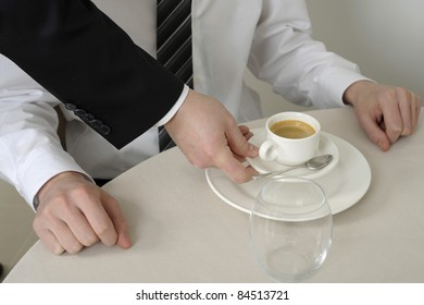 Waiter serving a coffee to a person sitting at a table