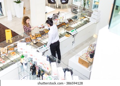 Waiter serving customer in a pastry shop, view from above - Woman buying cake and cookies for breakfast