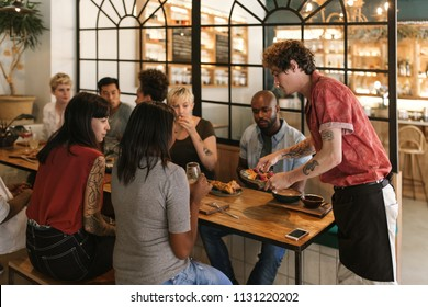 Waiter serving delicious freshly made food to a group of smiling young friends sitting together at a table in a bistro
