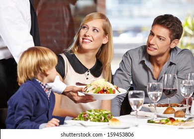 Waiter serving a family in a restaurant and bringing a full plate