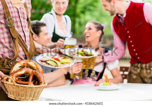 Waiter serving food in Bavarian beer garden, people eating and drinking in background