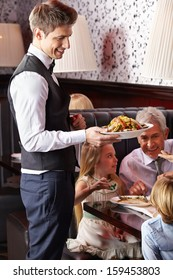 Waiter serving food to family in a restaurant