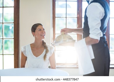 Waiter serving food to smiling women in restaurant