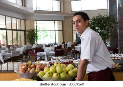 Waiter serving fresh fruits at restaurant.