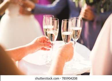 Waiter serving glasses with champagne on a tray
