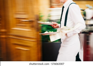 Waiter Serving In Motion On Duty in Restaurant Long Exposure