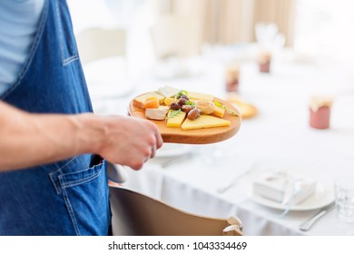 Waiter serving olives and cheese on wooden board.