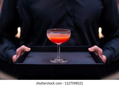 waiter serving red cocktail