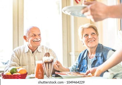Waiter serving senior retired couple eating cakes at fashion bio restaurant - Pension and active elderly concept with mature people having genuine fun together - Bright filter with focus on woman