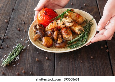 Waiter serving a shish kebab with tomato and mushrooms. Chief decorating food for presentation in small cafe. Waiter serving shish kebab with fresh vegetables for retail.