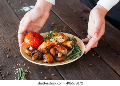 Waiter serving a shish kebab with tomato and mushrooms on wooden background. Chief decorating food for presentation in small cafe. Waiter serving shish kebab with fresh vegetables for retail.
