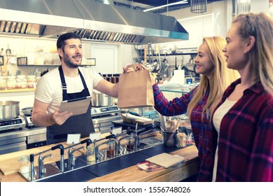 Waiter serving takeaway food to customers at counter in small family eatery restaurant – Smiling owner of trendy popular fast food delivering to clients a online to go order in recycled paper bag
