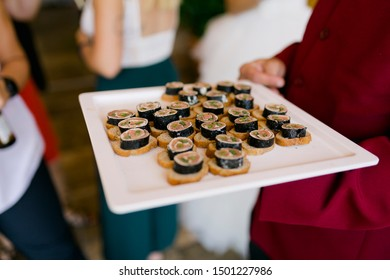 waiter serving tray of sushi at banquet