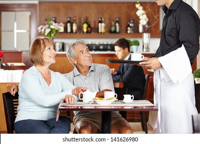Waiter serving two seniors in a coffee shop for breakfast