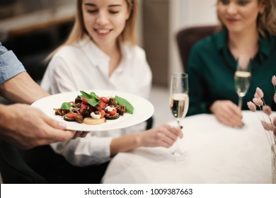Waiter serving vegetable salad in cafe, closeup