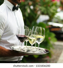 Waiter serving wine at a luxurious gathering.