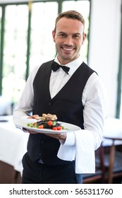 Waiter showing a dish in a commercial kitchen