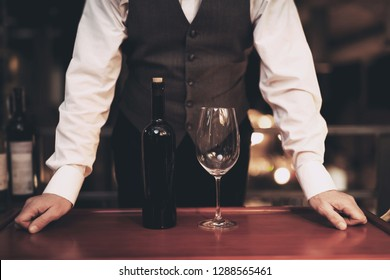 Waiter stands before tray with bottle of wine and empty glass in restaurant. Wine tasting concept. Professional degustation expert in winemaking.