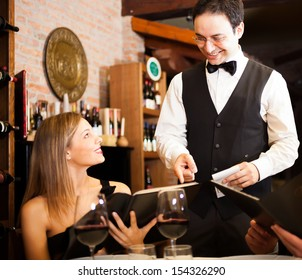Waiter suggesting food to a woman in a restaurant