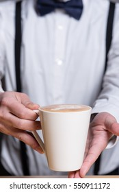 Waiter with suspenders handing over Cappuccino, closeup of cup, selective focus