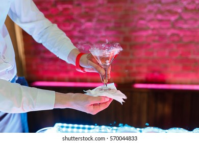 The waiter takes the hand with glass of bubbling champagne over pyramid during catering at party