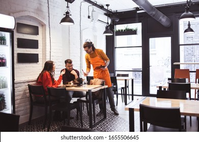 Waiter Takes Order From a young Couple