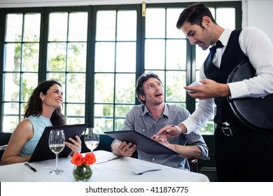 Waiter taking an order for a couple in a restaurant