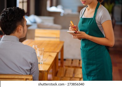 Waiter taking order from her customer in a restaurant