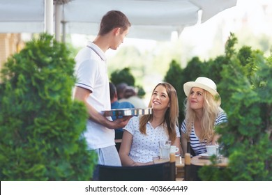 Waiter taking an order from the two beautiful young women sitting in an outdoor caffe