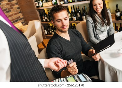 Waiter taking a payment by credit card at the restaurant