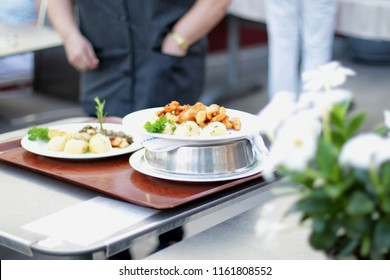 Waiter and a tray of food.