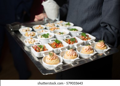 A waiter with a tray of snacks at a banquet