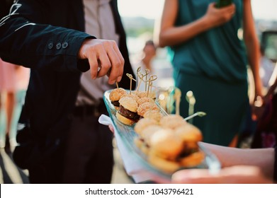 A waiter with a tray of snacks at a banquet or reception. Catering buffet at party